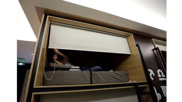 Zhang Shuang Jie, un ingeniero de la empresa Baishan, baja una cortina mientras se prepara para dormir alrededor de la medianoche en un cuarto individual en la oficina