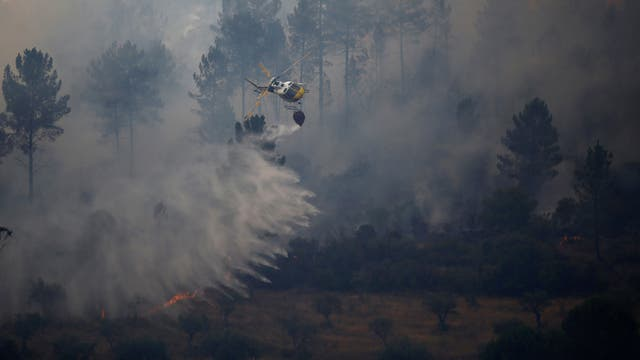 Un helicóptero de bomberos tira agua para extinguir un incendio forestal en Vila Velha de Rodao, cerca de Castelo Branco, Portugal.