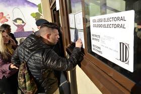 Un ciudadano revisa el padrón en un colegio electoral de Plaza España, en Barcelona