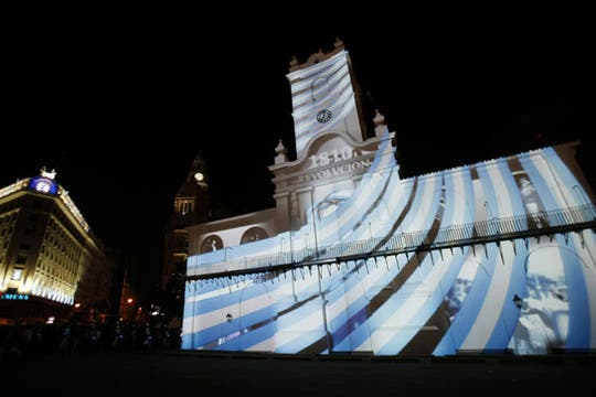 La bandera argentina, reflejada mediante una proyección basada en mapping, en las paredes del frente del Cabildo. Foto: EFE