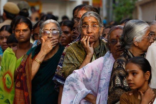 Mujeres esperan para entrar en el Ashram o predio de la comunidad espiritual de Sai Baba. Foto: AP