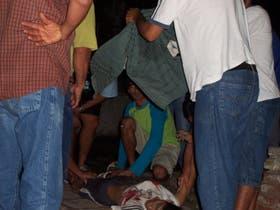 Tres imágenes de la violencia: rodeada, aparece la víctima mortal; la familia del chico muerto no encuentra consuelo; con la cara ensangrentada, uno de los policías heridos