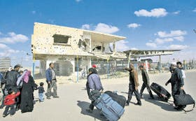 Palestinos que regresan a la Franja de Gaza caminan cerca de una vivienda que muestra las secuelas de la ofensiva militar israelí