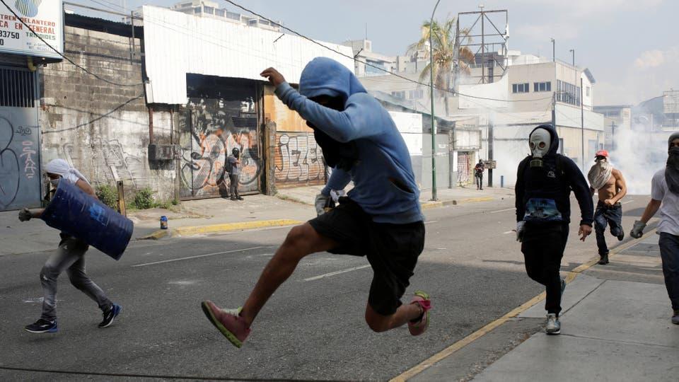 Varios manifestantes huyen de los gases que arroja la pilicía. Foto: Reuters / Marco Bello