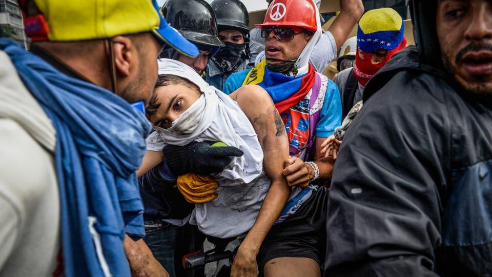 Un manifestante atropellado por un vehículo de la Guardia Nacional es cargado por otros manifestantes en Caracas. Foto: AFP / Federico Parra