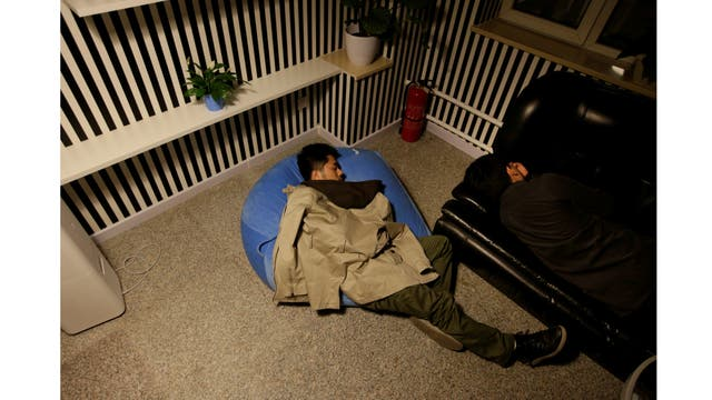 Yu Xiaojiang (LI) y Li Yan, los empleados de Grupo Gopal, toman una siesta durante un descanso en el trabajo alrededor de la medianoche
