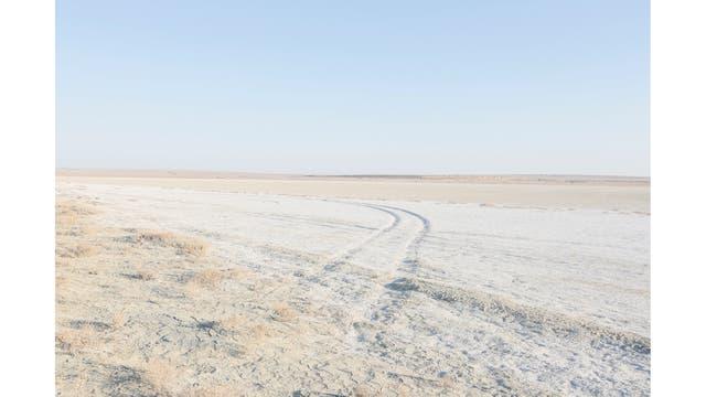 Huellas de autos a través de la tierra salina fuera de la aldea de Zhalanash, cerca del mar de Aral