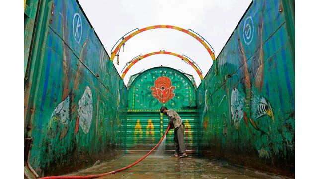 Un trabajador lava un camión decorado en Peshawar