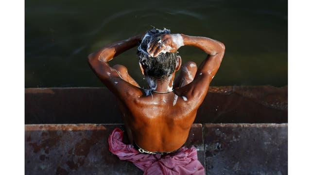 Un hombre se lava a orillas del río Ganges en Varanasi