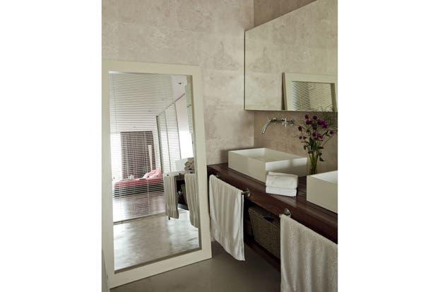 El baño principal tiene un revestimiento de travertino y un espejo de pared a pared..