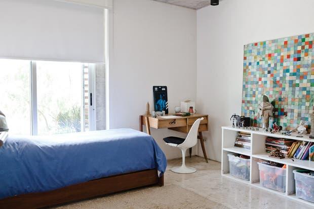 Arte a pleno en uno de los cuartos infantiles: una obra de Carlos Herrera sobre la pared, un biplano de colección en miniatura y un cuadro del dueño de casa apoyado sobre el mueble laqueado blanco..