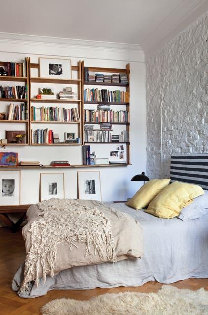 Respaldo de cama con funda de lino rayado, una biblioteca enchapada en zebrano (todo de Mesopotamia Buenos Aires) y un banco de lapacho (Net) ubicado debajo..  Foto:Living /Magalí Saberian