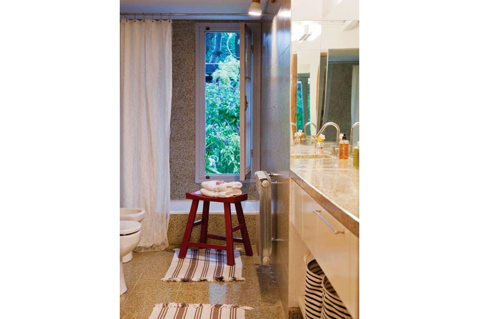 El granítico predominante en el baño se compensa con la onda net del aplique escandinavo, las alfombras bicolor (Ikea) y los canastos rayados (Sissy Boy, de Holanda).  Foto:Living /Magalí Saberian