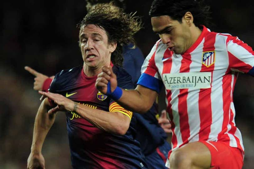 Puyol sufre la potencia de Falcao. Foto: AFP