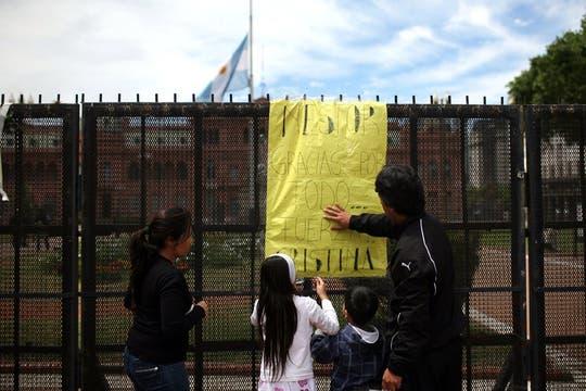 Dos niños con sus padres depositan un mensaje. Foto: LA NACION / Silvana Colombo
