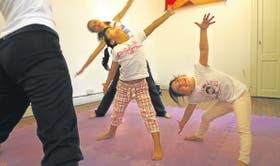 Tres niñas intentan imitar la posición de su maestra, Eugenia Danager, con quien toman clases dos veces por semana en Palermo