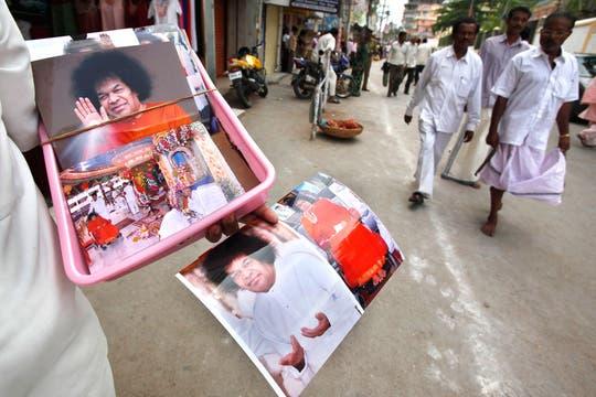 Un vendedor custodia la entrada al Ashram mientras miles esperan entrar para despedir a Sai Baba. Foto: AP