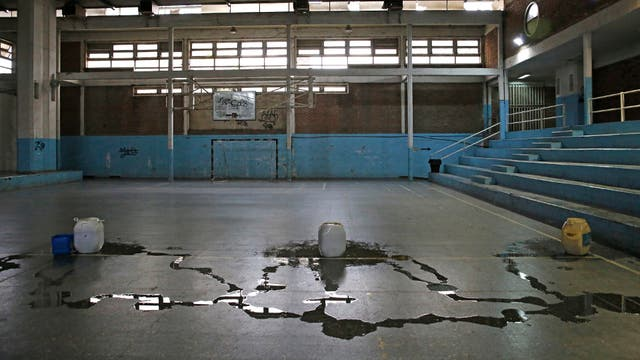 Polideportivo Chacabuco. Uno de los gimnasios internos tiene varias filtraciones en el techo; en un día de lluvia, las goteras invaden la cancha; al fondo se observan los vidrios rotos