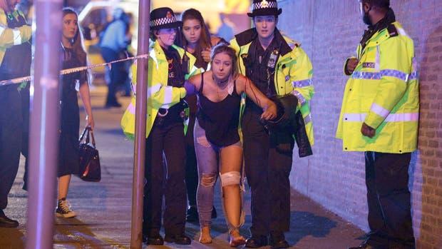 Atentado en Manchester: una joven es asistida por la policía después del ataque