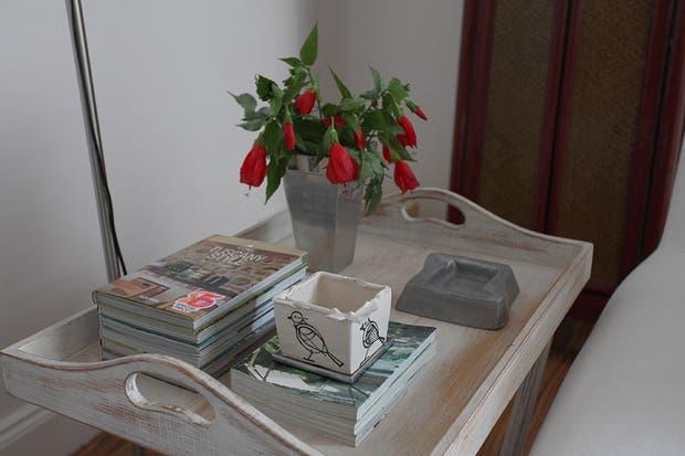 En primer plano, junto al sillón, bandeja con patas a modo de mesa lateral. Sobre ella, florero, cenicero, macetita ''chorreada ilustrada'' de loza ($65, Artefactos) y una colección personal de libros y revistas de deco y diseño. Foto: Guadalupe Aizaga