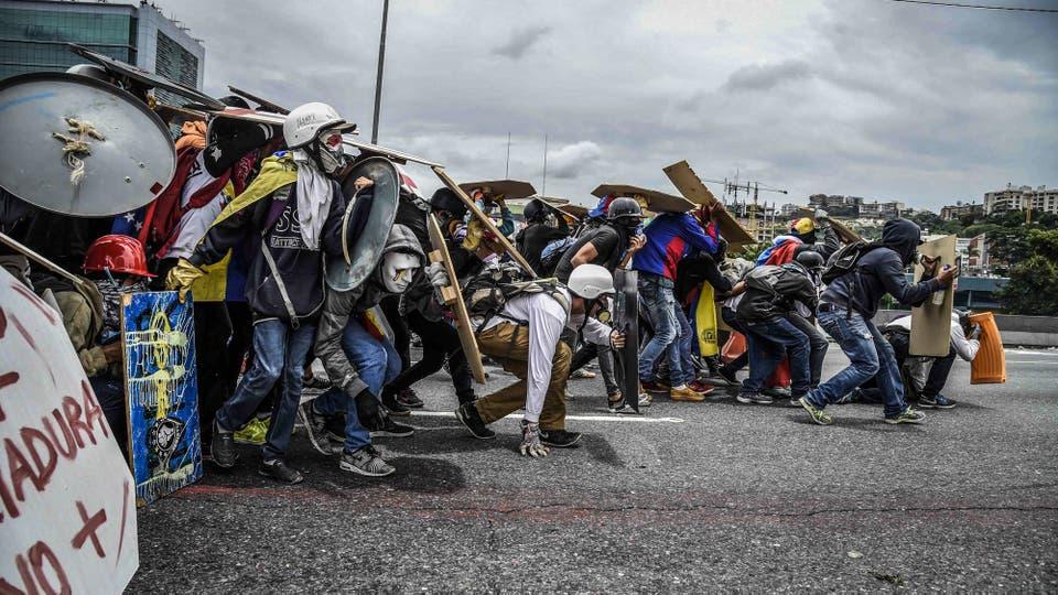 Manifestantes con escudos caseros y mascaras de gas chocan contra la policía antidisturbios en Caracas. Foto: AFP / Juan Barreto