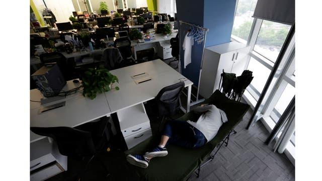 Kou Meng, director de producto de crédito Renren Management Co., duerme en una cama plegable en la oficina por la mañana temprano
