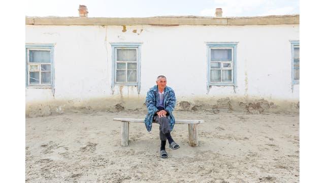 Erali Serimbetov, que nació en 1961, sentado frente a su casa rodeada de dunas en una remota parte de la aldea de Karateren