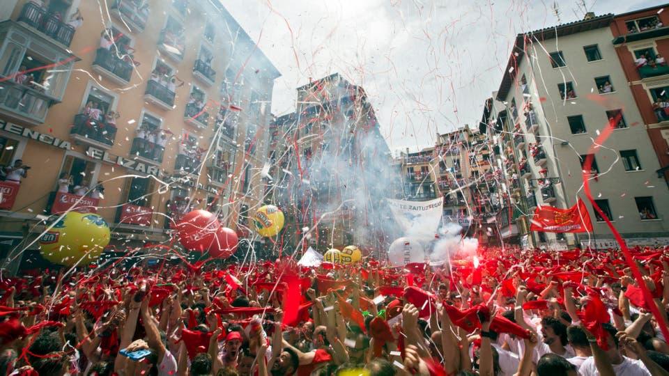 Cientos de personas alzan sus brazos al son de la música de los gaiteros que salen desde el Ayuntamiento de Pamplona para amenizar las calles del Casco Viejo de la ciudad tras el lanzamiento del tradicional chupinazo que ha abierto a las doce del mediodía las Fiestas de San Fermín. Foto: EFE / Jim Hollander