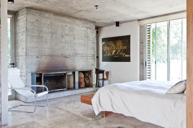 Junto a la chimenea de hormigón se luce un discreto sillón blanco, otro clásico diseño con la firma de Mies van der Rohe. Las cortinas son roller screen Thermoveil y blackout vinílico (Leval)..