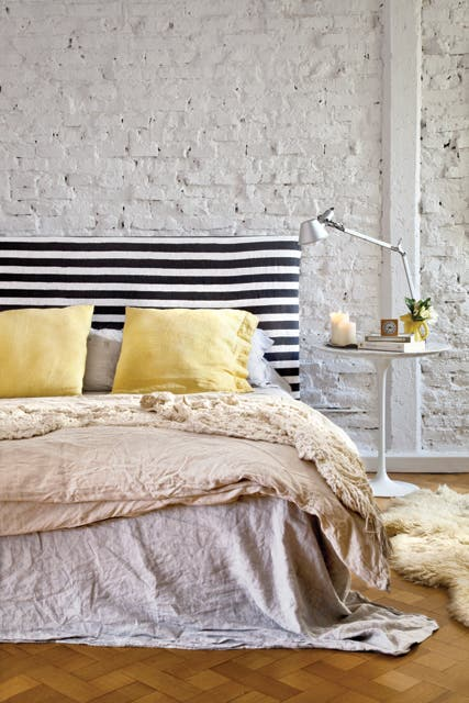 Como mesita de luz, dos clásicos contemporáneos: una 'Tulip' (Manifesto) con una lámpara 'Tolomeo'. La ropa de cama (Ramos Generales) suma calidez con diferentes texturas..  Foto:Living /Magalí Saberian