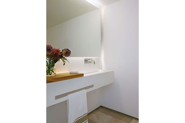 Para el toilette, planos continuos y líneas netas: espejo sin marco retroiluminado con LED, grifería de pared y mesada de mármol blanco con bacha incorporada y raja horizontal en lugar de toallero.  /Belén Imaz, gentileza Estudio Ábaton