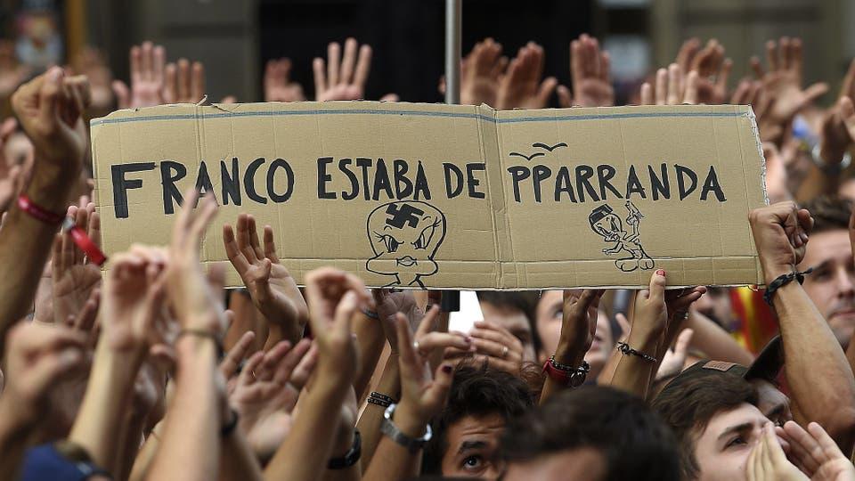 """Manifestantes muestran carteles con la leyenda """"Franco de estaba de fiesta"""" en relación a la represión policial durante las votaciones. Foto: AFP / Luis Gene"""