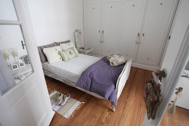 El dormitorio tiene doble acceso: desde el living y el pasillo. La cama, herencia de su abuelo, se restauró y patinó al igual que la mesa de luz que compró por Internet. Al otro lado, silla que su novio rescató de la basura y ella recicló, buscando mantener la pintura decapada por el tiempo. Foto: Guadalupe Aizaga
