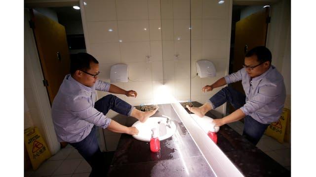 Liu Zhenyu, un administrador de clientes en Ju MEi You Pin, lava sus pies en el baño de la oficina antes de ir a dormir después de terminar el trabajo a la medianoche