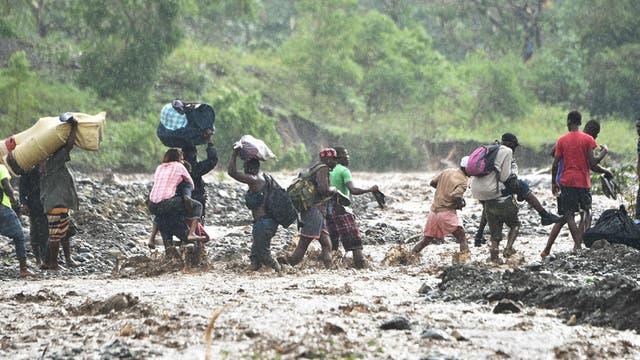 Haitianos cruzan el río La Digue en Petit Goave donde un puente cayó por las lluvias del huracán, al sur de la capital Port-au-Prince,