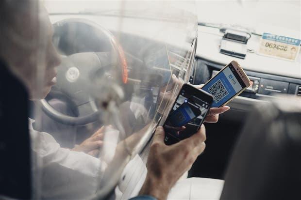 Un taxista sostiene un teléfono con un código QR para recibir el pago de un viaje