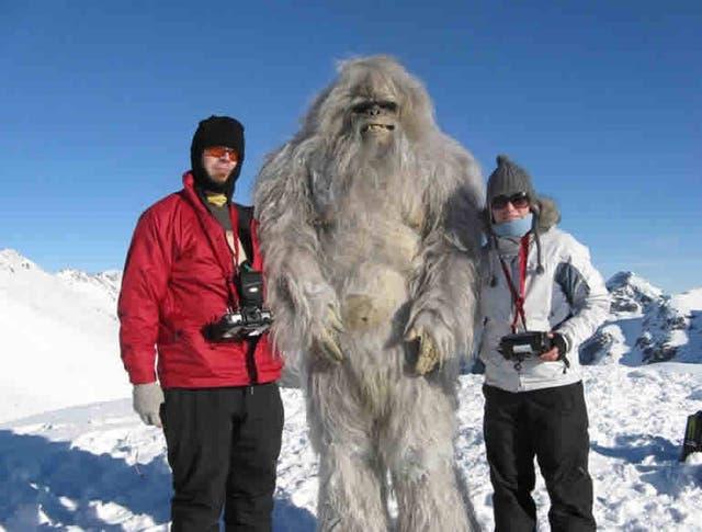Dos turistas en El Bolsón saludan al Yeti quien parece estar harto de las fotos o muy colgado