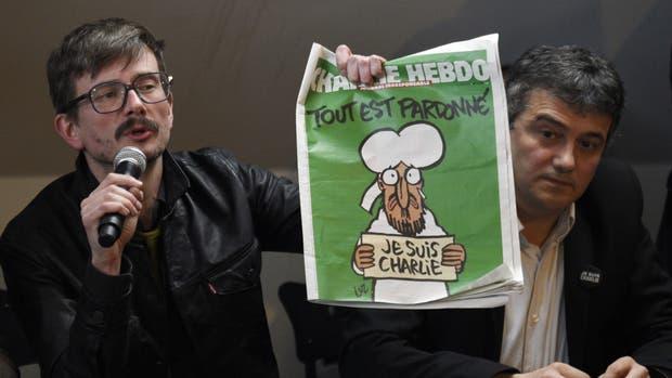 El dibujante Riss (izquierda) sostiene la edición de Charlie Hebdo que fue publicada luego del ataque terrorista que mató 12 de sus trabajadores, durante una conferencia de prensa en 2015