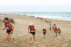 El pelotón de corredores deja la playa y se apresta a ingresar en el bosque