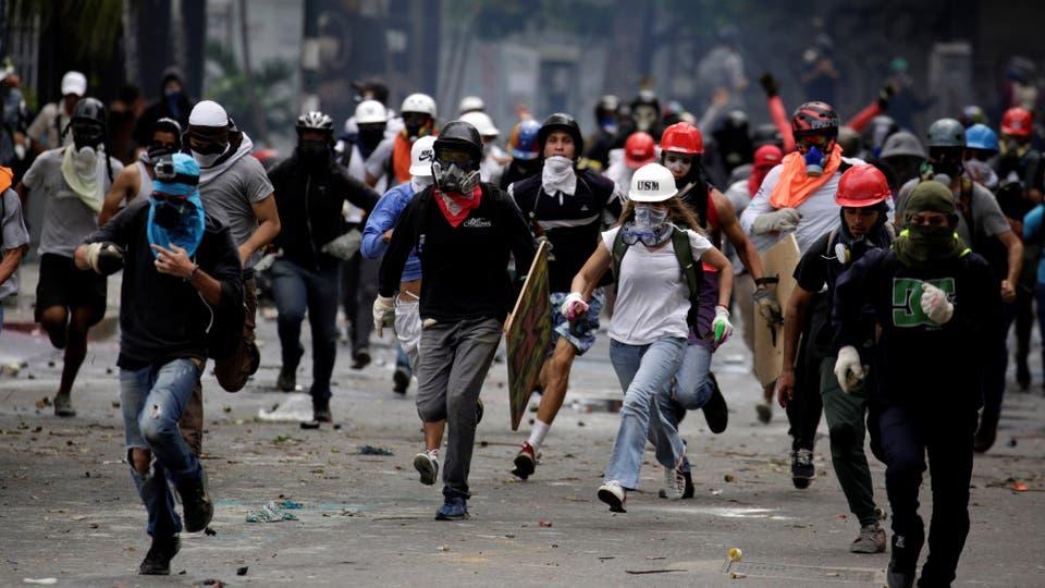 Los jóves huyen de los gases que arroja la policía. Foto: Reuters / Carlos Garcia Rawlins