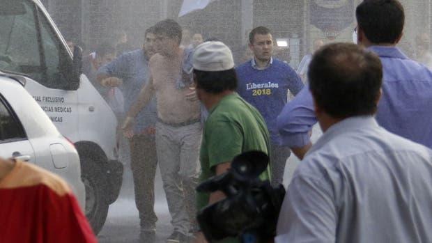 El presidente del Partido Liberal, Efraín Alegre, camina entre agua lanzada por policías paraguayos para disolver una protesta hoy.
