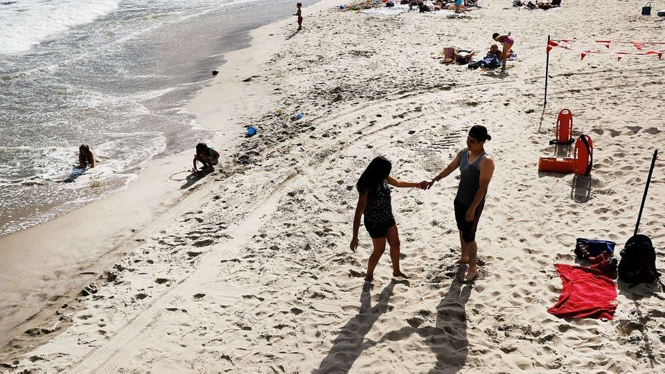 Los turistas disfrutan de la playa en Coney Island, las temperaturas superaron el promedio normal para ésta época del año. Foto: AFP