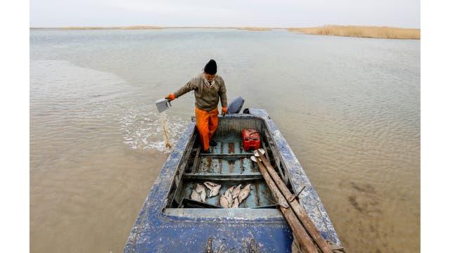 Un pescador saca agua de su bote en la costa del mar de Aral, en las afueras del pueblo de Karateren