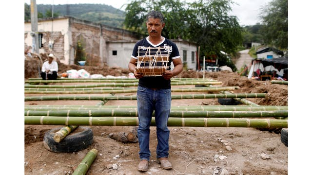 Héctor Guzmán, de 48 años, campesino y representante del Presidente Municipal de San José Platanar, sostiene el modelo de una casa nueva para su padre