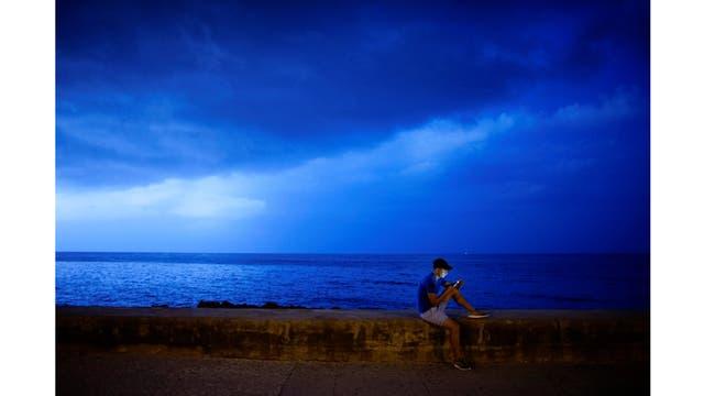 Un joven se conecta a internet en el malecón de La Habana
