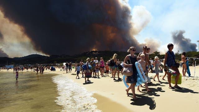 La gente sale de la playa con sus pertenencias mientras un incendio arde un bosque detrás de ellos en Bormes-les-Mimosas, sureste de Francia.