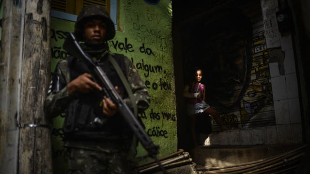 Una niña observa a un soldado fuertemente armado durante una operativo militar en la favela Rocinha
