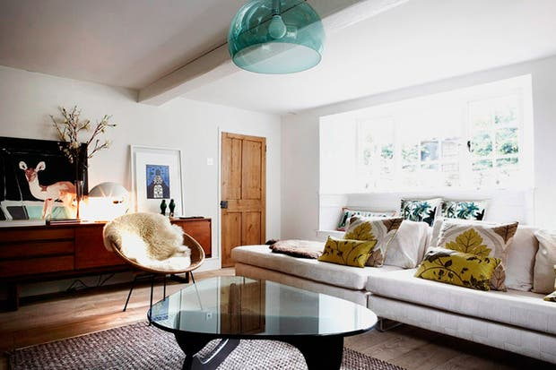 La puerta en madera natural contrasta con el blanco del ambiente. Contra la pared, un mueble recuperado sirve como espacio de guardado..
