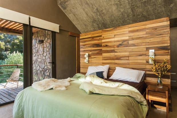 En el dormitorio principal, un volumen revestido en madera hace las veces de cabezal de la cama matrimonial y, del otro lado, contiene la mesada del baño..