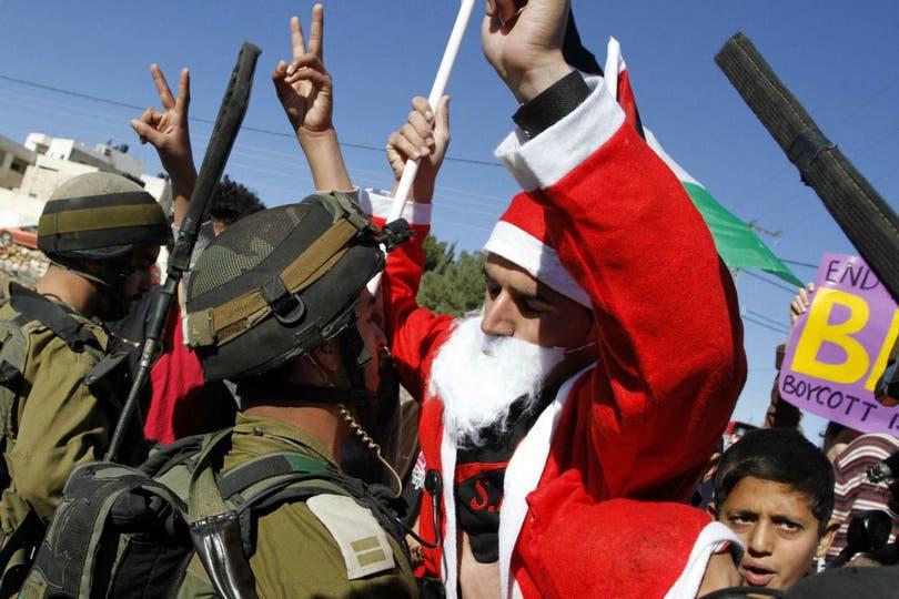 Manifestante palestino disfrazado de Papá Noel cara a cara con un soldado israelí. Foto: AFP